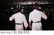 Купить «Two men in kimono walking on a parking lot holding a training swords on their shoulders», видеоролик № 30306910, снято 8 июля 2020 г. (c) Константин Шишкин / Фотобанк Лори