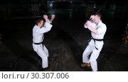 Купить «Two young men in kimono training on a parking lot. Sword fight», видеоролик № 30307006, снято 8 июля 2020 г. (c) Константин Шишкин / Фотобанк Лори