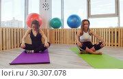 Купить «Young women doing fitness sitting in the studio. Bending their back», видеоролик № 30307078, снято 25 марта 2019 г. (c) Константин Шишкин / Фотобанк Лори