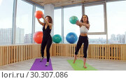 Купить «Young women doing fitness in the studio holding a ball. Warming up», видеоролик № 30307086, снято 25 марта 2019 г. (c) Константин Шишкин / Фотобанк Лори
