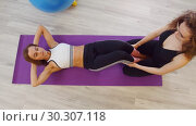 Купить «Young women doing fitness in the studio. A woman pumping her abs laying on the yoga mat while another woman holding her legs», видеоролик № 30307118, снято 25 марта 2019 г. (c) Константин Шишкин / Фотобанк Лори