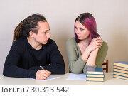 Купить «Молодая девушка и  подросток смотрят друг на друга за столом», фото № 30313542, снято 14 марта 2019 г. (c) Гетманец Инна / Фотобанк Лори