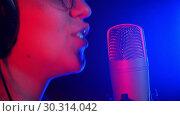 Купить «A young smiling woman in headphones singing in the studio. Neon lighting», видеоролик № 30314042, снято 23 марта 2019 г. (c) Константин Шишкин / Фотобанк Лори