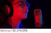 Купить «A young woman in glasses and headphones recording a song in the studio», видеоролик № 30314058, снято 23 марта 2019 г. (c) Константин Шишкин / Фотобанк Лори