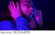 Купить «Emotional young woman in headphones singing in the studio. Purple neon lighting», видеоролик № 30314070, снято 23 марта 2019 г. (c) Константин Шишкин / Фотобанк Лори