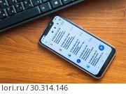 Купить «Смартфон с мошенническими смс сообщениями лежит на столе рядом с компьютерной клавиатурой», эксклюзивное фото № 30314146, снято 23 февраля 2019 г. (c) Алёшина Оксана / Фотобанк Лори