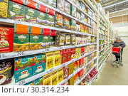 Купить «Russia Samara March 2019: A beautiful mature woman thought about buying tea supermarket. Text in Russian: tea, black, may, discount», фото № 30314234, снято 1 марта 2019 г. (c) Акиньшин Владимир / Фотобанк Лори