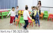 Купить «Happy kids and female teacher playing musical chairs together during break in classroom at elementary school», видеоролик № 30323026, снято 30 января 2019 г. (c) Яков Филимонов / Фотобанк Лори
