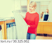Купить «Mature female shopper searching for suitable fabric», фото № 30325002, снято 15 февраля 2017 г. (c) Яков Филимонов / Фотобанк Лори
