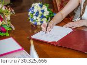Купить «Невеста ставит подпись в документах о заключение брака во Дворце бракосочетания», фото № 30325666, снято 26 июля 2018 г. (c) Алёшина Оксана / Фотобанк Лори