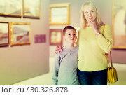 Купить «Cheerful mom and son exploring paintings», фото № 30326878, снято 18 марта 2017 г. (c) Яков Филимонов / Фотобанк Лори