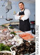 Купить «Seller in black apron showing fish on his counter», фото № 30326902, снято 27 октября 2016 г. (c) Яков Филимонов / Фотобанк Лори