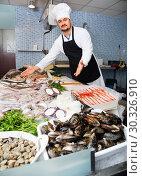 Купить «Seller in white cap and black apron showing counter with fish», фото № 30326910, снято 27 октября 2016 г. (c) Яков Филимонов / Фотобанк Лори