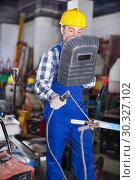 Купить «Smiling guy using welder for construction work», фото № 30327102, снято 17 января 2017 г. (c) Яков Филимонов / Фотобанк Лори