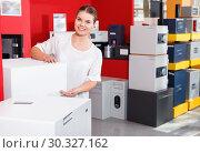 Купить «Young attractive saleswoman offering home safe in specialty shop», фото № 30327162, снято 17 апреля 2018 г. (c) Яков Филимонов / Фотобанк Лори