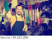 Купить «Seller displaying various items in garden equipment shop», фото № 30327206, снято 2 марта 2017 г. (c) Яков Филимонов / Фотобанк Лори