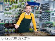 Купить «Positive male seller demonstrating assortment», фото № 30327214, снято 2 марта 2017 г. (c) Яков Филимонов / Фотобанк Лори