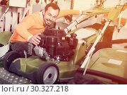 Купить «Purchaser checks lawnmower», фото № 30327218, снято 2 марта 2017 г. (c) Яков Филимонов / Фотобанк Лори