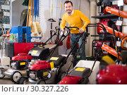 Купить «Smiling man deciding on best lawnmower in garden equipment shop», фото № 30327226, снято 2 марта 2017 г. (c) Яков Филимонов / Фотобанк Лори