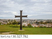 Купить «Cross near Bagrati Cathedral on the background of the cityscape of Kutaisi, Georgia», фото № 30327782, снято 27 сентября 2018 г. (c) Юлия Бабкина / Фотобанк Лори