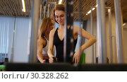 Купить «Young women doing fitness in the gym. A woman doing strength exercises. Another woman watching her and tries it», видеоролик № 30328262, снято 25 марта 2019 г. (c) Константин Шишкин / Фотобанк Лори