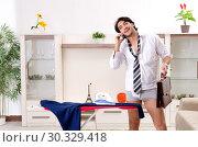 Купить «Young man ironing in the bedroom», фото № 30329418, снято 29 ноября 2018 г. (c) Elnur / Фотобанк Лори