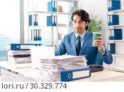 Купить «Young handsome male employee with too much work in the office», фото № 30329774, снято 10 ноября 2018 г. (c) Elnur / Фотобанк Лори