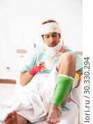 Купить «Young injured man staying in the hospital», фото № 30330294, снято 2 октября 2018 г. (c) Elnur / Фотобанк Лори