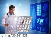 Купить «Doctor in telemedicine concept looking at x-ray image», фото № 30341338, снято 21 марта 2019 г. (c) Elnur / Фотобанк Лори