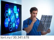 Купить «Doctor in telemedicine concept looking at x-ray image», фото № 30341678, снято 21 марта 2019 г. (c) Elnur / Фотобанк Лори