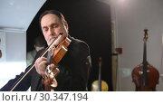 Купить «Скрипичный мастер, реставратор музыкальных инструментов Музея музыки Владимир Якимов играет на скрипке на открытии Всероссийской выставки скрипичных мастеров в Шереметевском дворце - Музее музыки, Санкт-Петербург», видеоролик № 30347194, снято 18 марта 2019 г. (c) Stockphoto / Фотобанк Лори