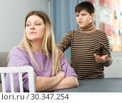Upset mother sitting at table after arguing with son indoors. Стоковое фото, фотограф Яков Филимонов / Фотобанк Лори