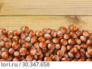 Купить «Unpeeled hazelnut on wooden surface closeup», фото № 30347658, снято 20 марта 2019 г. (c) Яков Филимонов / Фотобанк Лори
