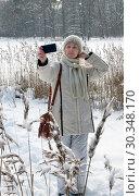 Купить «The young woman in a white jacket makes a selfie on the coast of the winter forest lake», фото № 30348170, снято 1 января 2015 г. (c) Куликов Константин / Фотобанк Лори
