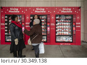 Купить «Just in time for #givingtuesday, volunteers explain the â. œGiving Machines' outside the LDS Church in New York on Giving Tuesday, November 27, 2018. The...», фото № 30349138, снято 27 ноября 2018 г. (c) age Fotostock / Фотобанк Лори