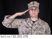 Купить «Shoulder portrait of saluting United States Marine Corps infantry in camo uniform and eight-pointed utility cap or cover with USMC Eagle, Globe, and Anchor emblem, studio shoot on black background.», фото № 30355378, снято 22 октября 2017 г. (c) age Fotostock / Фотобанк Лори