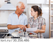 Купить «Perplexed woman and senior man with mixer tap and paper», фото № 30356486, снято 19 июня 2018 г. (c) Яков Филимонов / Фотобанк Лори