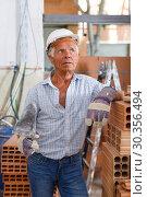 Купить «Thoughtful foreman near stack of bricks», фото № 30356494, снято 19 июня 2018 г. (c) Яков Филимонов / Фотобанк Лори