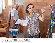 Купить «Thoughtful woman looking at list of works», фото № 30356502, снято 19 июня 2018 г. (c) Яков Филимонов / Фотобанк Лори