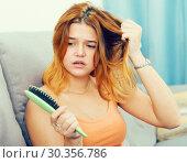 Купить «Young woman is nervous because her hair suffers from avitaminosis», фото № 30356786, снято 17 июля 2019 г. (c) Яков Филимонов / Фотобанк Лори