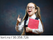 Купить «Smart Schoolgirl Hold Book Point Index Finger up», фото № 30358726, снято 2 февраля 2019 г. (c) Иван Карпов / Фотобанк Лори