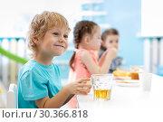 Купить «Children boy and girls at daycare lunch table», фото № 30366818, снято 7 декабря 2019 г. (c) Оксана Кузьмина / Фотобанк Лори