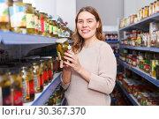 Купить «Female customer holding pickle goods in the food store», фото № 30367370, снято 11 апреля 2018 г. (c) Яков Филимонов / Фотобанк Лори