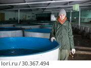 Купить «Woman watching fish in pool on farm», фото № 30367494, снято 4 февраля 2018 г. (c) Яков Филимонов / Фотобанк Лори