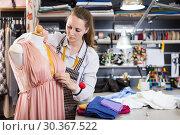 Woman professional sewer measuring dress at mannequin workshop. Стоковое фото, фотограф Яков Филимонов / Фотобанк Лори