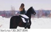 Купить «A happy young woman with long hair riding a horse in a village. Standing on snowy ground», видеоролик № 30367894, снято 23 июля 2019 г. (c) Константин Шишкин / Фотобанк Лори