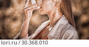 Купить «Woman using asthma inhaler», фото № 30368010, снято 17 июля 2019 г. (c) Wavebreak Media / Фотобанк Лори