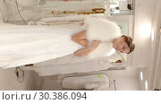 Купить «Сheerful young woman dressed in luxury white gown standing in wedding shop», видеоролик № 30386094, снято 16 октября 2018 г. (c) Яков Филимонов / Фотобанк Лори