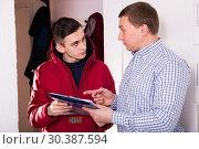 Купить «Young courier is delivering order for adult man», фото № 30387594, снято 5 февраля 2018 г. (c) Яков Филимонов / Фотобанк Лори