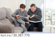 Купить «Father and teen son solve school assignment together», фото № 30387770, снято 8 февраля 2019 г. (c) Яков Филимонов / Фотобанк Лори
